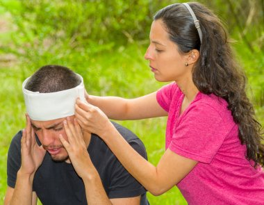 Young man with head injury receiving treatment and bandage around skull from woman, outdoors environment