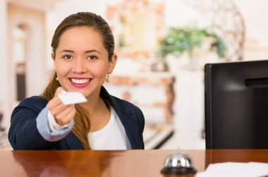 Young brunette hotel receptionist with friendly smile handing over key to client across desk, customers point of view