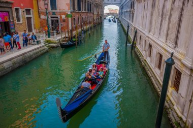 VENICE, ITALY - JUNE 18, 2015: Beautiful view of people meeting Venice on gondola transportation, water ways with a sunny nice day