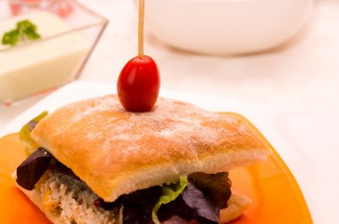 Delicious ciabatta sandwich with skewered cherry tomato top, sitting on white plate, catering concept