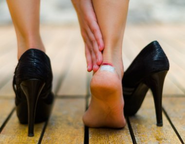 High heels sometimes hurts, little white patch in ankle. Black high heels on wooden floor