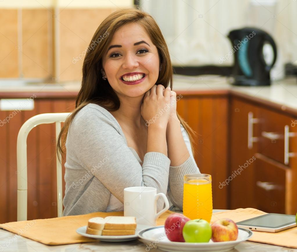 Young pretty brunette sitting by breakfast table smiling to camera, fruits, juice and coffee placed in front, hostel environment