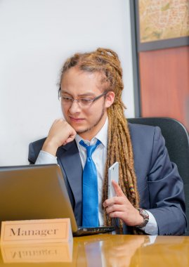 Handsome man with dreads and business suit sitting by desk, holding mobile phone while looking at laptop, young manager concept