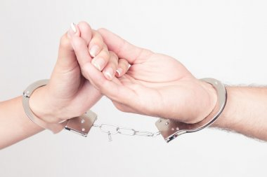 Man and womans hands handcuffed together