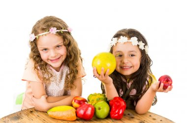 Beautiful healthy little girls holding delicious fresh fruits and vegetables