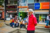Unidentify uomo indigeno che funziona la piantagione di caffè shopping nella via commerciale principale di Armenia, Colombia