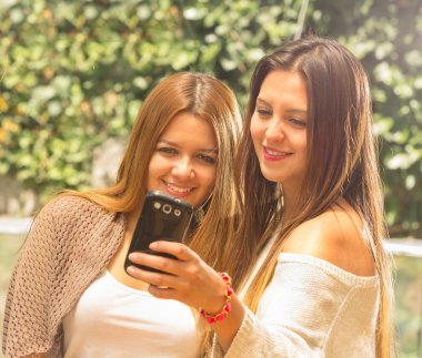 Girls outdoors looking at phone