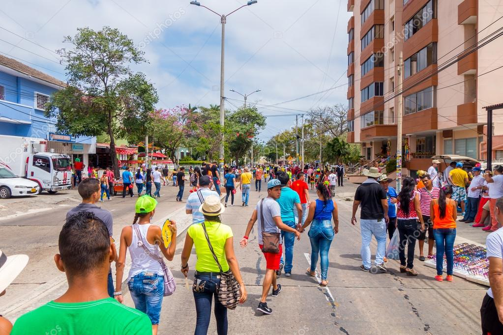 Multiple spectators street waking away from the Carnival parade colorful vendors in Colombias most important folklore celebration Barranquilla, Colombia