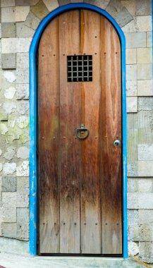 Ancient style rustic wooden door with small metal bar window