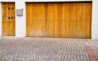 Wooden light colored entrance and garage door with stone tiles in front
