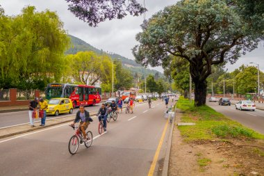 Unidentified hispanic cyclists moving through vehicle free street with heavy traffic in opposite lane divided by trees Candelaria area Bogota, Colombia
