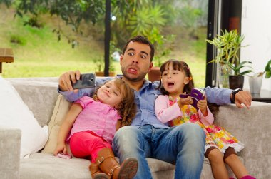 Family portrait of father and two daughters sitting together in sofa posing for selfie making funny faces