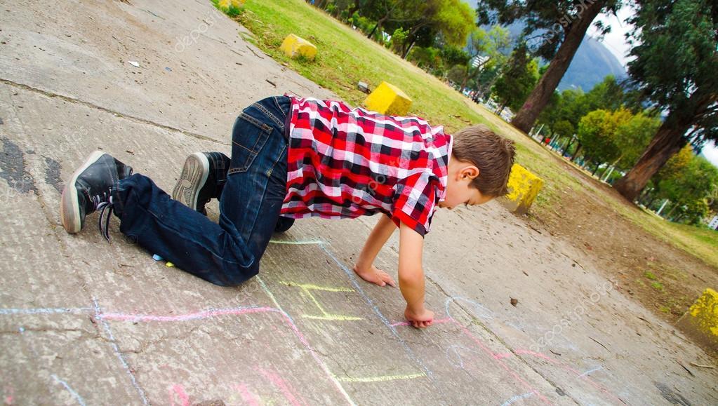 Sweet boy drawing playing hopscotch