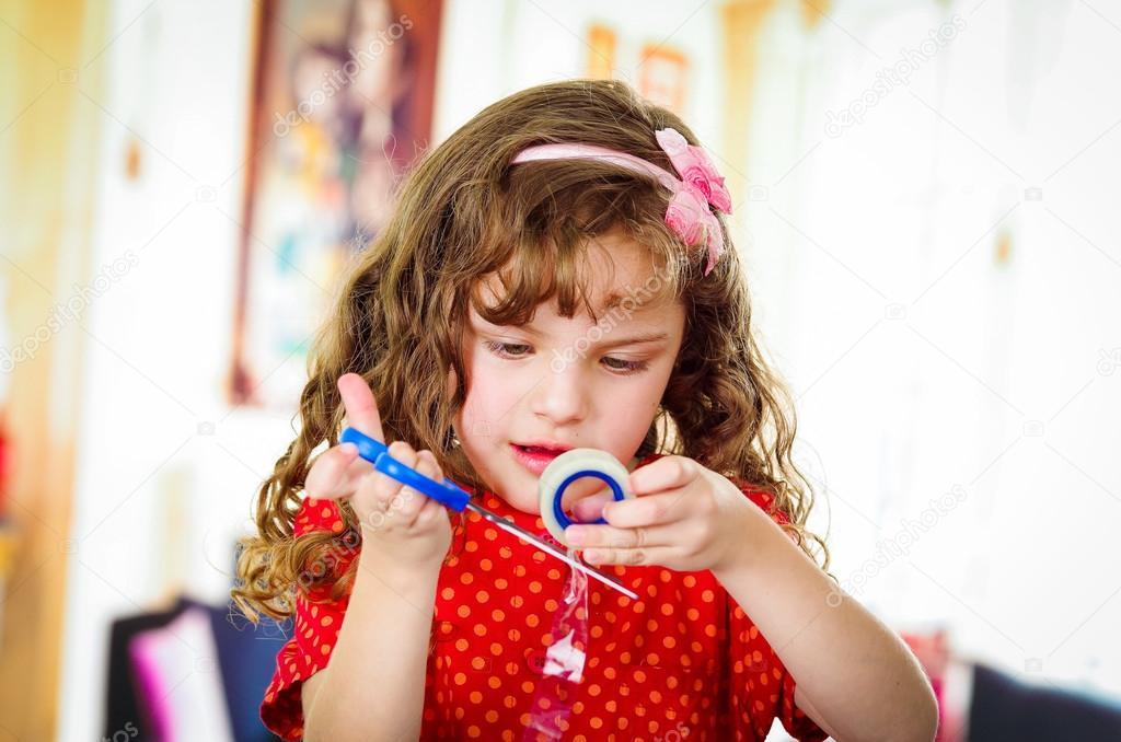 Kleine Mädchen schneiden Klebeband — Stockfoto © pxhidalgo #81330004