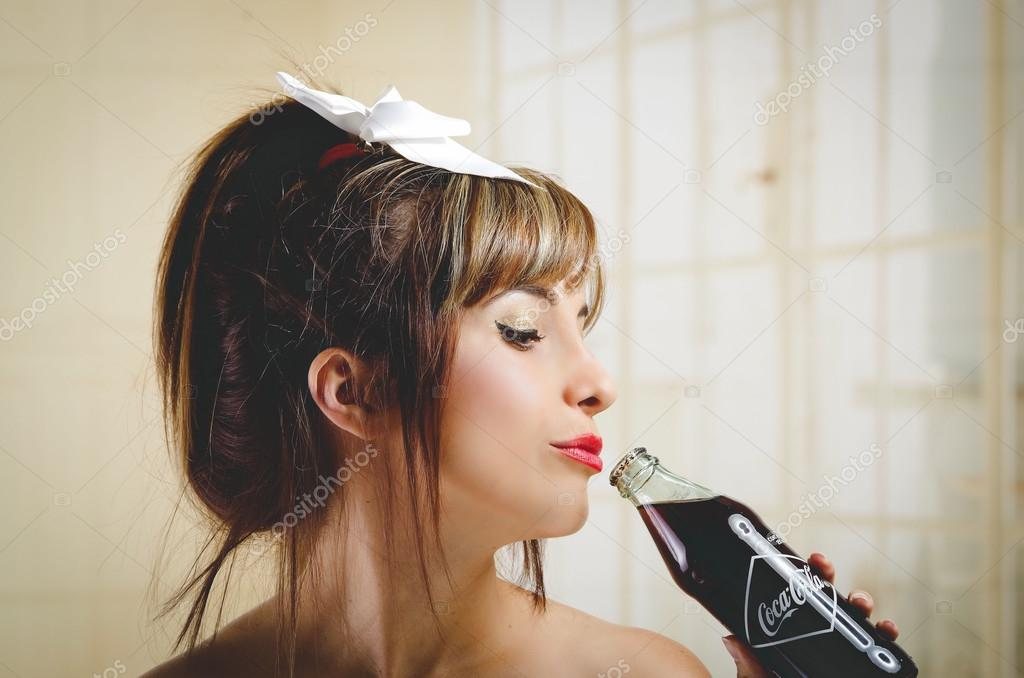 Beautiful retro girl holding an old vintage coca cola bottle
