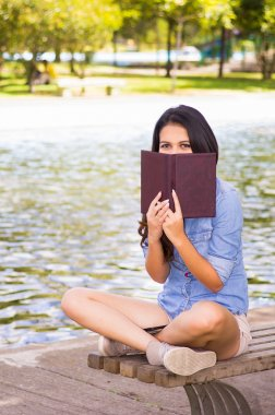 Brunette model wearing denim shirt and white shorts relaxing in park environment, sitting on bench next to lake hiding face behind book