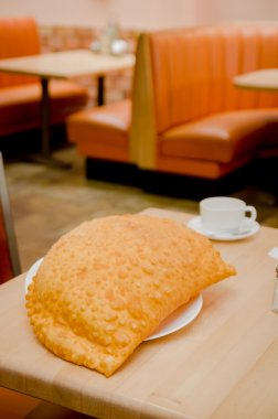 Beautiful large yellow colored empanada sitting on small white plate in restaurant setting