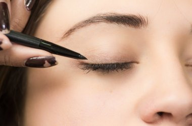 Closeup headshot brunette getting makeup treatment by professional stylist applying eyeliner