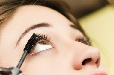 Closeup headshot brunette getting makeup treatment by professional stylist applying mascara on eyelashes