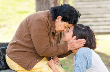 Grandmother facing granddaughter touching heads outdoors, lovely picture displaying love between people