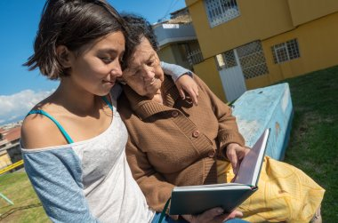 Lovely grandmother and granddaughter sitting together enjoying quality time outdoors reading in book