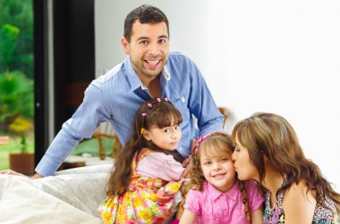 Beautiful hispanic family of four posing naturally while sitting in white sofa