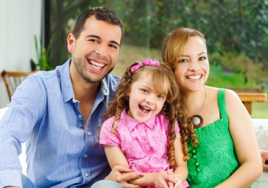 Proud happy hispanic parents posing with little cute girl wearing pink clothes in front of window garden background