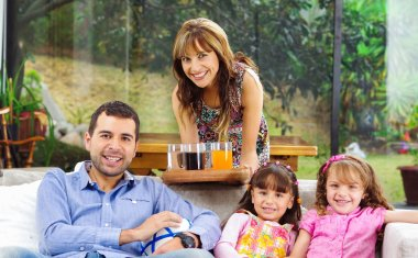 Hispanic father sitting in sofa with two daughters and mother leaning over from behind serving tray of drinks, garden background