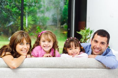 Beautiful hispanic family of four posing with heads sticking up from back sofa looking at camera smiling