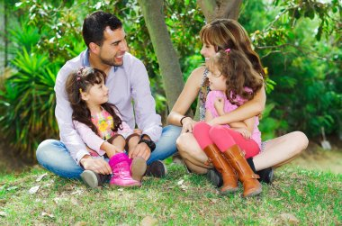 Beautiful hispanic family of four sitting outside on grass engaging in conversations while posing naturally and happily