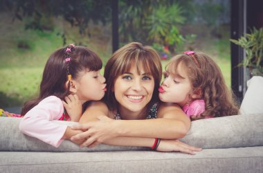 Hispanic mother in sofa with two daughters kissing her cheeks from each side, blurry garden background
