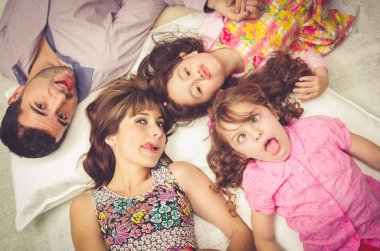 Young adorable hispanic sisters and parents lying down with heads touching, bodies spread out different directions closeup