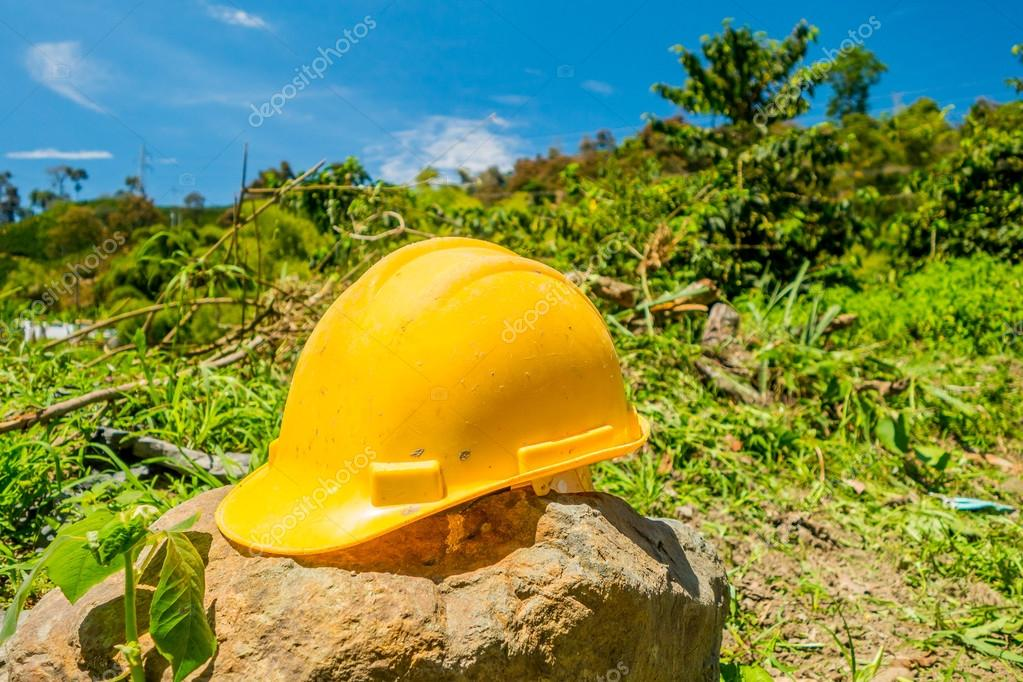 Yellow hard hat with a coffee plantation farm in the background