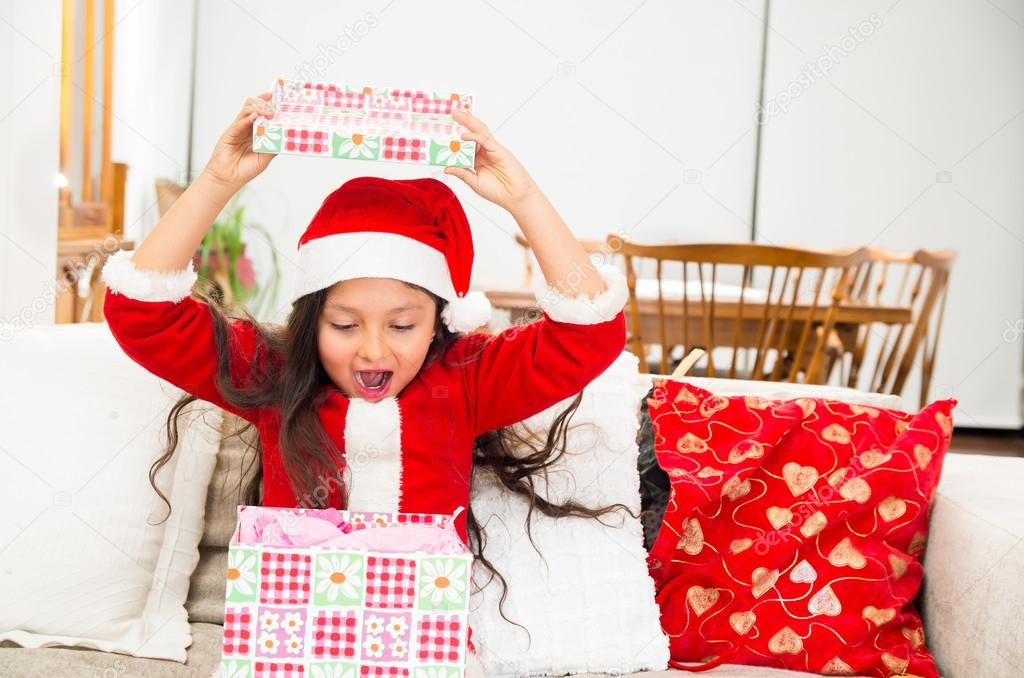 ab543c411f98 Cute excited surprised little girl in Christmas dress opening present —  Photo by ...