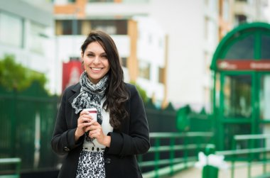 Brunette model wearing black jacket and grey scarf waiting for public transportation acting cold at station with cup of coffee