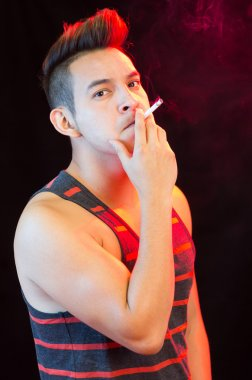 Hispanic male wearing red black striped singlet posing with serious facial expression and smoking a cigarette smoke visible