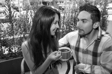 Hispanic cute couple enjoying coffee during a cozy date outdoors and green vegetation background, black white edition