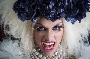 Closeup drag queen wearing spectacular makeup, glamorous trashy look, posing with open mouth for camera
