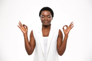Peaceful attractive african american young woman meditating and keeping calm