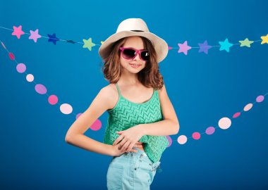 Cheerful cute little girl in sunglasses standing and posing