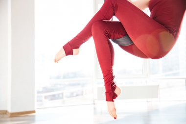 Slim woman legs doing aerial yoga exercise in studio