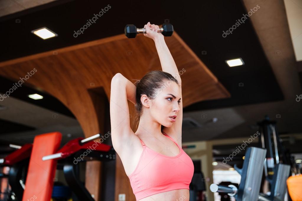 Ernsthafte Sportlerin Übungen für Muskeln der Arme mit Kurzhanteln ...