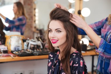 hairdresser making hairstyle to cheerful woman with long hair