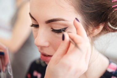 Makeup artist doing false lashes to young woman in curlers