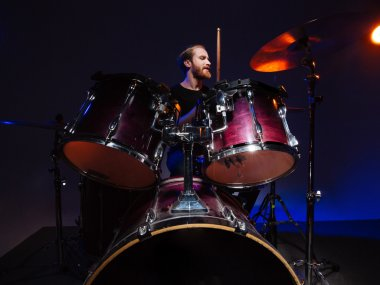 Attractive bearded man drummer sitting and playing on his kit