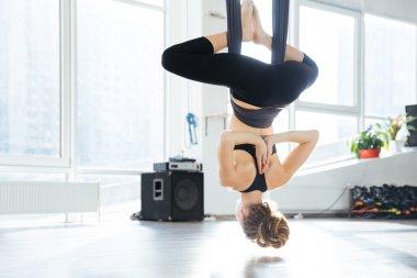 Attractive young woman doing antigravity yoga using hammock