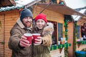 Fotografie Happy couple offering hot drinks to you on christmas market