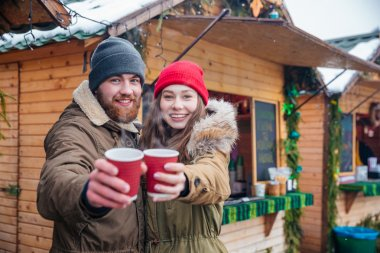 Happy couple offering hot drinks to you on christmas market