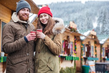 Happy couple drinking coffee on christmas market in mountain resort