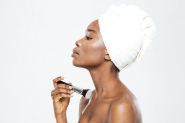Afro american woman applying makeup with brush